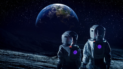 Two Astronauts in Space Suits Standing on the Moon and Look at Beautiful Earth in the Sky. Space Travel, Habitable World and Colonization Concept.