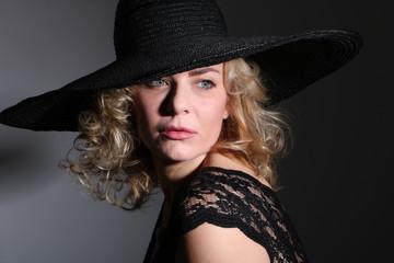 Junge blonde Frau mit Hut blickt nachdenklich