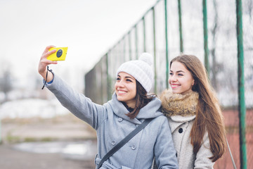 Two millennial teenage girls taking a selfie outdoors in winter using smart phone, smiling. No makeup, natural lighting