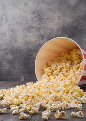 Popcorn scattered from a striped bucket (red and white box) isolated on grey wooden table (background). Selective focus. Copy space. Nobody.
