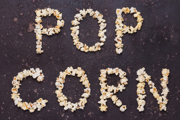 Popcorn lettering (inscription) isolated on brown stone background. Nobody.