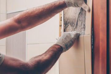 Working with his hands carefully removes old tiles from the wall