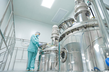 Pharmaceutical factory woman worker in protective clothing operating production line in sterile environment