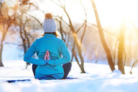Meditating girl practicing yoga in winter morning holding hands in namaste behind her back