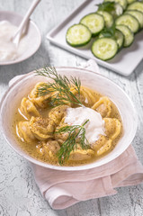 Pelmeni - meat dumplings with sour cream in broth. Russian national dish, rustic