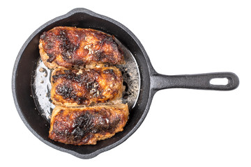 Roasted chicken pieces in cast iron pan top view, isolated