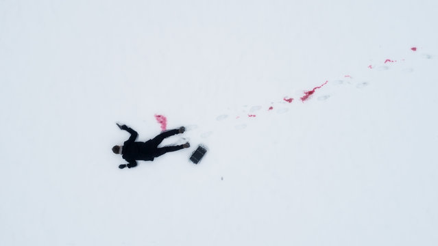 Dead man on snow with gun and case of cash