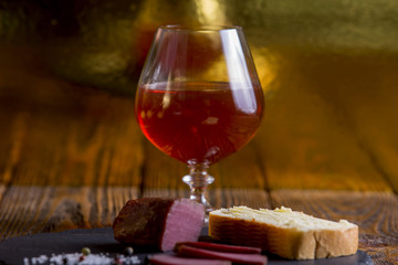 A glass of cognac stands on a wooden table with meat and lemons