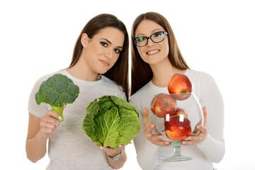 Girl holding red apples and girl holding vegelables