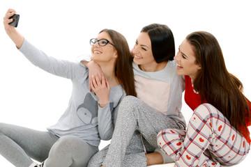 Three beautiful happy girls ih their pajamas taking selfie with smartphone