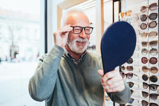 Handsome senior man choosing eyeglasses frame in optical store.