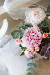 Wedding bouquet of peonies lying on the chair