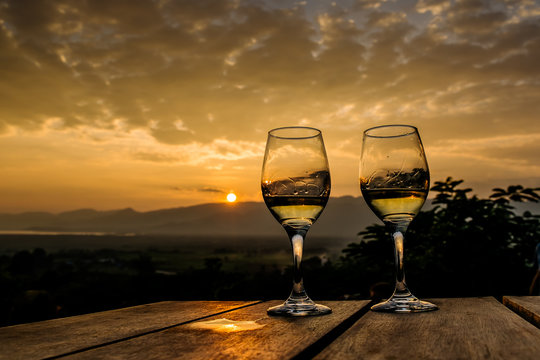 two glasses of wine in the background landscape with dramatic sky during sunset. The mountains in Myanmar, Inle lake