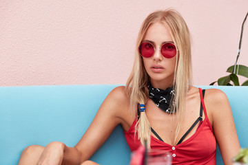 Fashionable young female model in trendy sunglasses, feels relaxed while sits on comfortable blue sofa against pink background. Stylish blonde woman poses indoor at cafe alone. Rest concept.