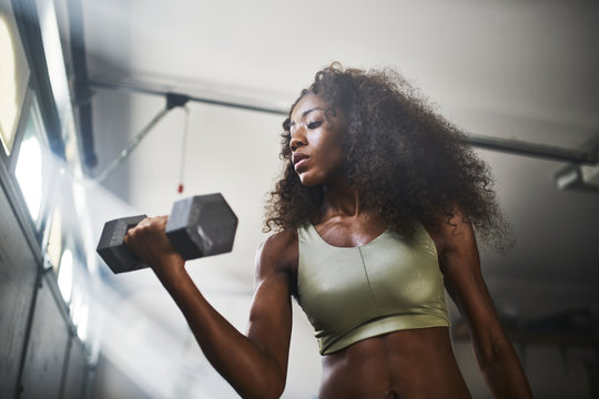 fit african american woman working out by lifting weights in home gym