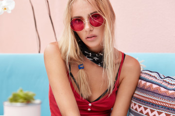 People, fashion and recreation concept. Adorable young woman wears red sunglasses, sits in restaurant, drinks tasty cocktail, feels relaxed, has serious expression. Fashionable female poses indoor