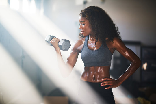 fit african american woman lifting iron in home gym