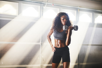 fit athletic african american woman lifting weights inside home gym in
