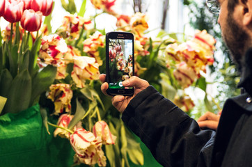 The hand with the phone makes a photo of flowers on flowers exhibition. People using mobile phones, people making photos, using technology concept