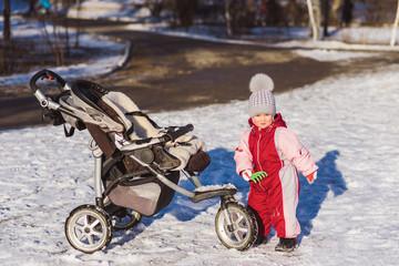little child plays near a stroller in winter