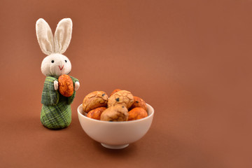 Easter Bunny with Eggs stock images. Easter bunny on a brown background. Spring decoration images. Easter concept. Cute white rabbit toy