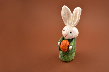 White rabbit toy stock images. Easter bunny on a brown background. Easter rabbit with egg. Spring decoration images. Easter concept