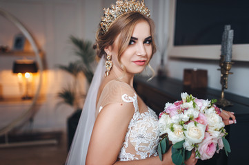 Beautiful bride with a golden crown on her head. The bride in a lace dress is standing in the interior.