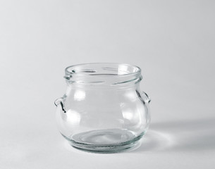 empty glass jar for honey on a light surface