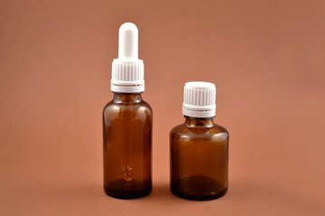 Two brown vials stock images. Empty cosmetic bottle. Vials on a brown background. Brown glass containers. Brown chemical glass