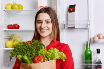 Positive female comes from grocery store with paper bag full of fresh ripe vegetables, going to put them in fridge, has happy expression. Woman vegeterian keeps to healthy diet. Eating concept