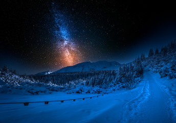 Fototapete - Mountain path and milky way in winter