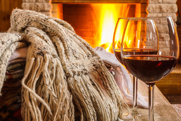 Glasses of wine against cozy fireplace background, winter vacation.