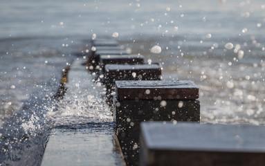 water from wave splashing over groyne in bay