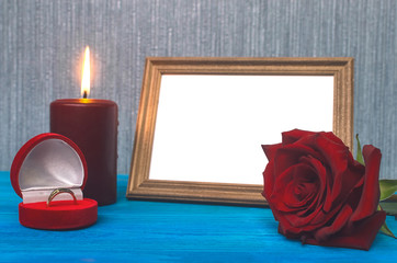 Wedding ring in a gift present box and empty photo frame of a loved one copy space and red rose flower on wooden table background. Marriage offer template. The proposal concept.