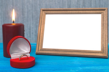 Wedding ring in a gift present box and empty photo frame of a loved one copy space and burning candle on wooden table background. Marriage offer template. The proposal concept.