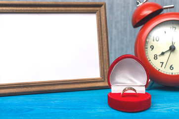Wedding ring in a gift present box and empty photo frame of a loved one copy space and red alarm clock on wooden table background. Marriage offer template. The proposal concept.