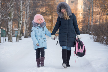 young mother leads the daughter from school