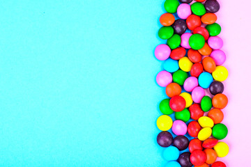 Small colored candy on bright background