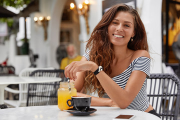 Portrait of glad satisfied pretty woman with dark hair, has positive expression, spends spare time at cozy restaurant, drinks fresh juice and coffee, looks joyfully into camera. People, emotions, rest