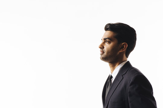 A profile portrait of a handsome man in suit and tie looking to side  isolated on white studio background