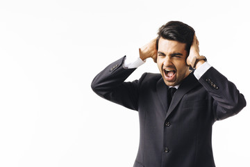 Stressed man in business suit and tie screaming and holding head, isolated on white