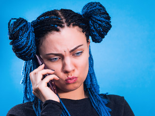 Young beautiful angry woman with african blue braids talking on her phone. Portrait of attractive fashion looking girl model. Hipster girl making dissatisfied unhappy face.