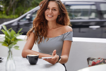 Happy female enterpreneur checks online email box, recreats during summer vacations, recieves good news concerning business, uses smart phone for communication, drinks hot coffee or cappuccino