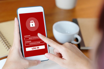 Hand using smart phone with password login at office desk background, cyber security concept