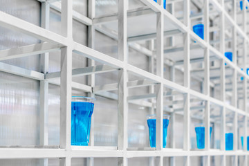 Blue water inside clear plastic cup on white metal shelf structure for decoration.