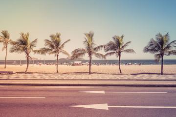 Beach with palms behind the asphalt road. Ipanema Beach, Rio de Janeiro, Brazil. Light effect
