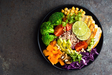 Buddha bowl meal with chicken fillet, brown rice, avocado, pepper, tomato, broccoli, red cabbage, chickpea, fresh lettuce salad, pine nuts and walnuts. Healthy balanced eating. Overhead view