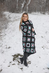 Beautiful girl with long hair in a long handmade knitted sweater
