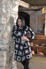 Beautiful brunette girl with long hair in a long handmade knitte