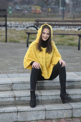 Pretty girl in a yellow handmade knitted poncho sitting on the s